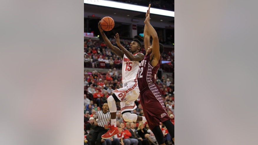 Ohio State's Kam Williams, left, makes a basket past Colgate's Jordan Robertson during the first half of an NCAA college basketball game Saturday, Dec. 6, 2014, in Columbus, Ohio. (AP Photo/Jay LaPrete)