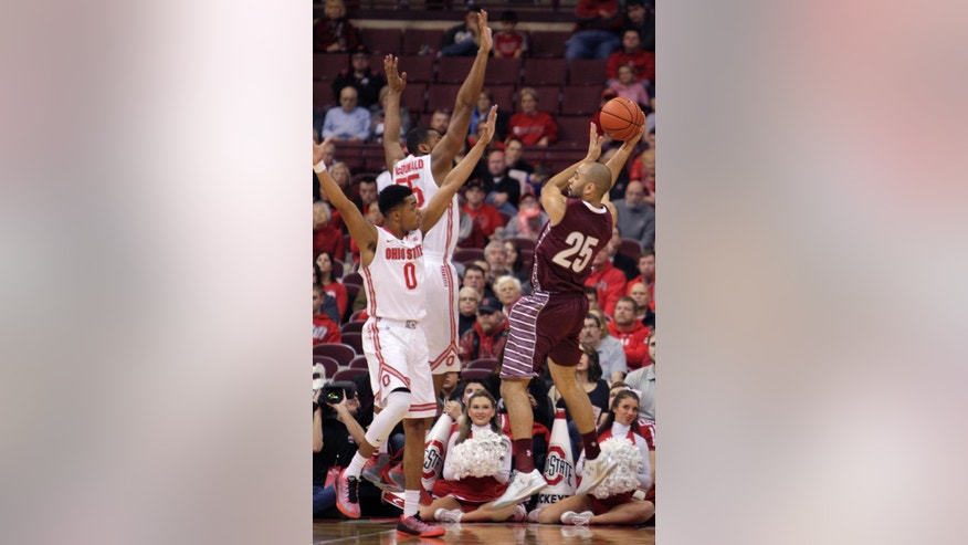 Colgate's Damon Sherman-Newsome, right, looks for an open pass as Ohio State's D'Angelo Russell (0) and Trey McDonald defend during the first half of an NCAA college basketball game Saturday, Dec. 6, 2014, in Columbus, Ohio. (AP Photo/Jay LaPrete)