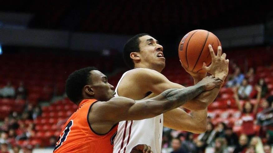 Washington State's Dexter Kernich-Drew, right, is fouled on the way to the basket by UTSA's Christian Wilson during the first half of an NCAA college basketball game in Pullman, Wash., Saturday, Dec. 6, 2014. (AP Photo/Young Kwak)