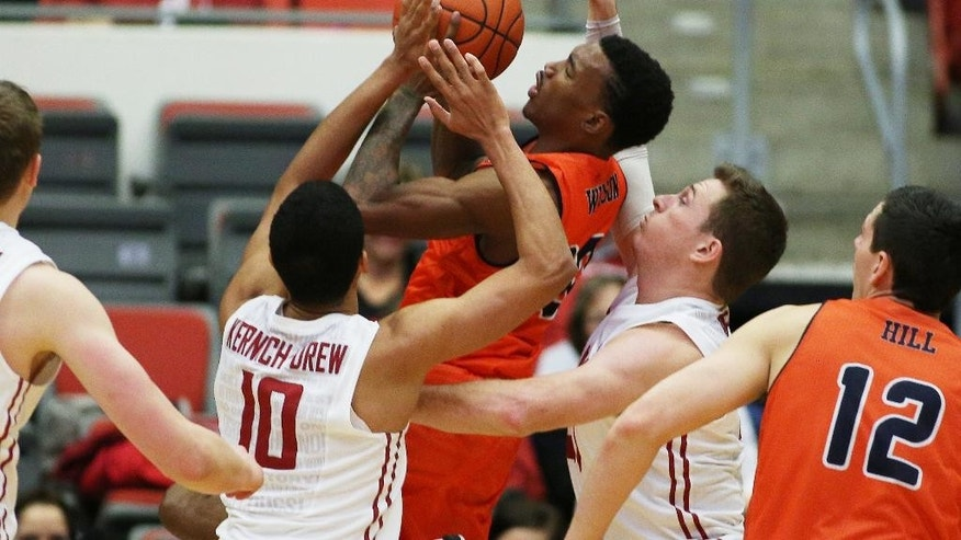 UTSA's Christian Wilson, center, takes a shot against Washington State's Dexter Kernich-Drew (10) and Brett Boese, right, during the first half of an NCAA college basketball game in Pullman, Wash., Saturday, Dec. 6, 2014. (AP Photo/Young Kwak)
