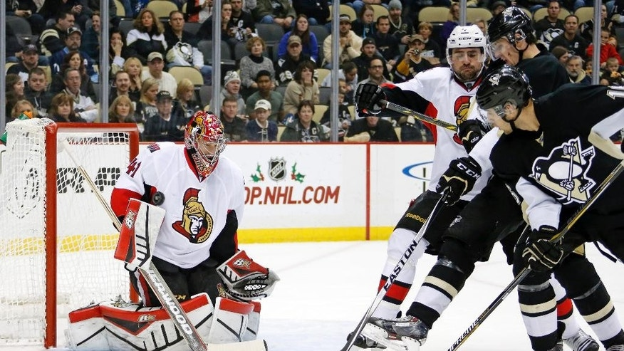 Pittsburgh Penguins' Brandon Sutter, right, deflects a shot by Penguins' Olli Maatta over the shoulder of Ottawa Senators goalie Craig Anderson (41) for a second-period goal during an NHL hockey game in Pittsburgh, Saturday, Dec. 6, 2014. (AP Photo/Gene J. Puskar)