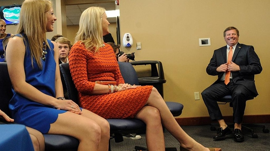 Jim McElwain, right, Florida's new head football coach, waites to be introduced as his daughter JoHanna, left, and wife Karen, center, look on during an NCAA college football news conference, Saturday, Dec. 6, 2014, in Gainesville, Fla.  (AP Photo/Phil Sandlin)