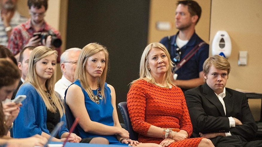 The family of Florida's new head football coach, Jim McElwain, listens as he speaks to the media during an NCAA college football news confernce Saturday, Dec. 6, 2014, in Gainesville, Fla. They are from left, Elizabeth, JoHanna, wife Karen, and son Jerret.   (AP Photo/Phil Sandlin)
