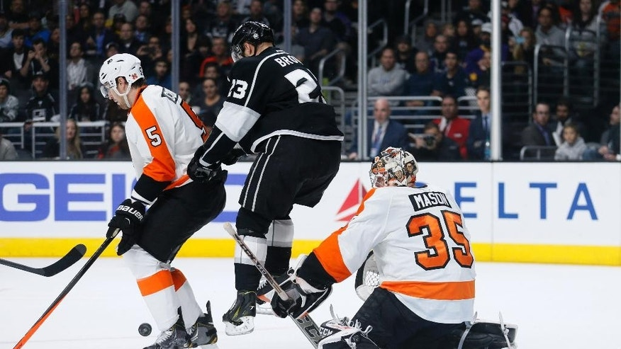 Philadelphia Flyers goalie Steve Mason, right, looks to prevent Los Angeles Kings' Dustin Brown, center, from scoring while Flyers defenseman Braydon Coburn, left, also defends during the second period of an NHL hockey game, Saturday, Dec. 6, 2014, in Los Angeles. (AP Photo/Danny Moloshok)