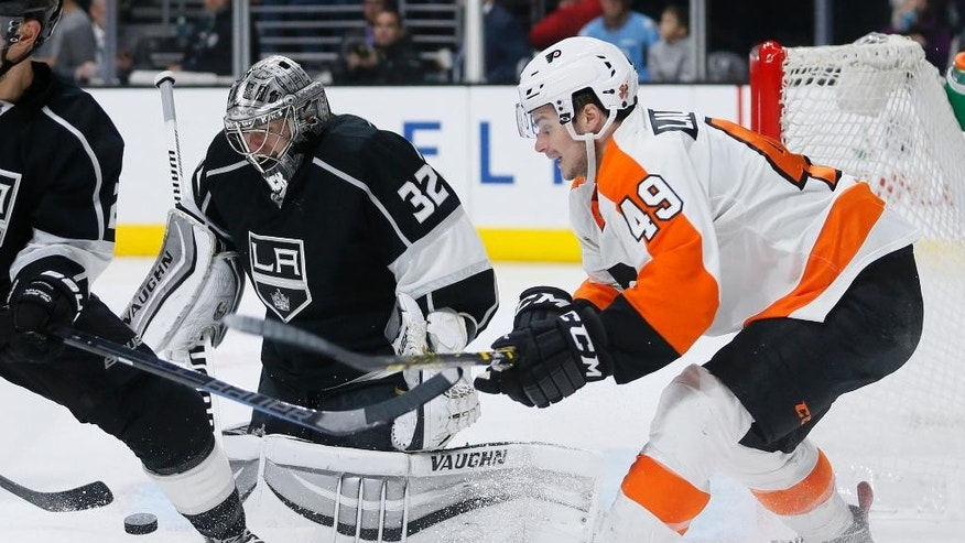 Los Angeles Kings goalie Jonathan Quick (32) prevents Philadelphia Flyers center Scott Laughton, right, from scoring during the third period of an NHL hockey game, Saturday, Dec. 6, 2014, in Los Angeles. (AP Photo/Danny Moloshok)