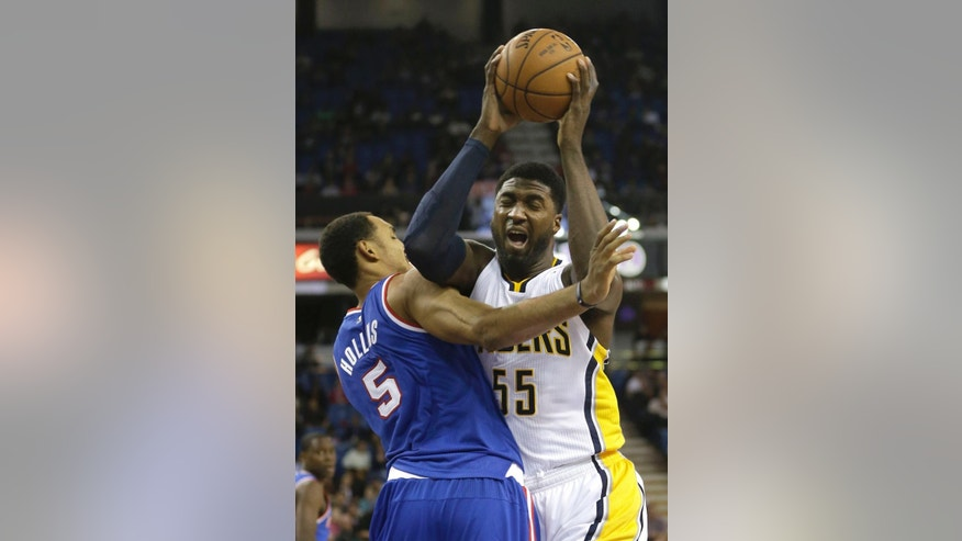 Indiana Placers center Roy Hibbert, right, goes to the basket against Sacramento Kings center Ryan Hollins during the first quarter of an NBA basketball game in Sacramento, Calif., Friday, Dec. 5, 2014. (AP Photo/Rich Pedroncelli)