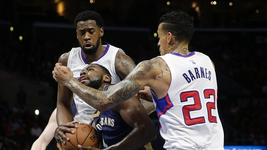 New Orleans Pelicans' Tyreke Evans, center, is defended by Los Angeles Clippers' Matt Barnes, right, and DeAndre Jordan during the first half of an NBA basketball game Saturday, Dec. 6, 2014, in Los Angeles. (AP Photo/Jae C. Hong)