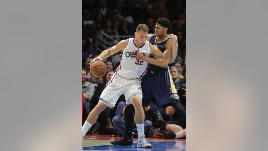 Los Angeles Clippers' Blake Griffin, left, is defended by New Orleans Pelicans' Anthony Davis during the first half of an NBA basketball game Saturday, Dec. 6, 2014, in Los Angeles. (AP Photo/Jae C. Hong)