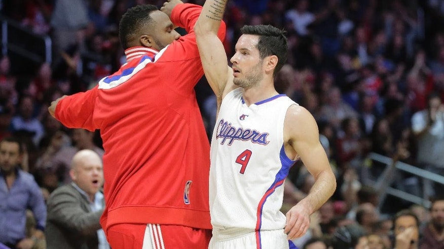 Los Angeles Clippers' J.J. Redick, right, high-fives teammate Glen Davis after making a 3-point basket during the first half of an NBA basketball game against the New Orleans Pelicans, Saturday, Dec. 6, 2014, in Los Angeles. (AP Photo/Jae C. Hong)