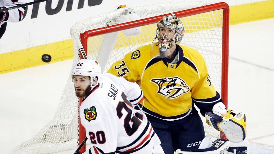 Chicago Blackhawks left wing Brandon Saad (20) chases a rebound in front of Nashville Predators goalie Pekka Rinne (35), of Finland, in the third period of an NHL hockey game Saturday, Dec. 6, 2014, in Nashville, Tenn. (AP Photo/Mark Humphrey)