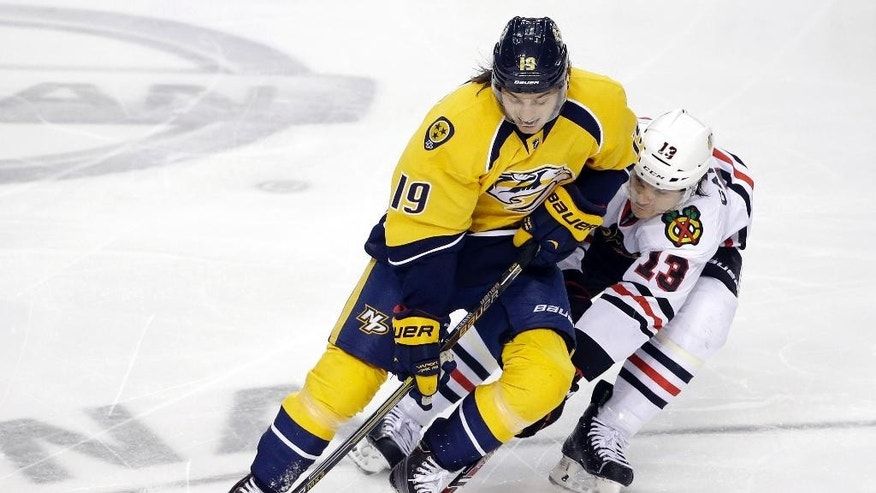 Chicago Blackhawks left wing Daniel Carcillo (13) tries to slow down Nashville Predators center Calle Jarnkrok (19), of Sweden, in the third period of an NHL hockey game Saturday, Dec. 6, 2014, in Nashville, Tenn. (AP Photo/Mark Humphrey)
