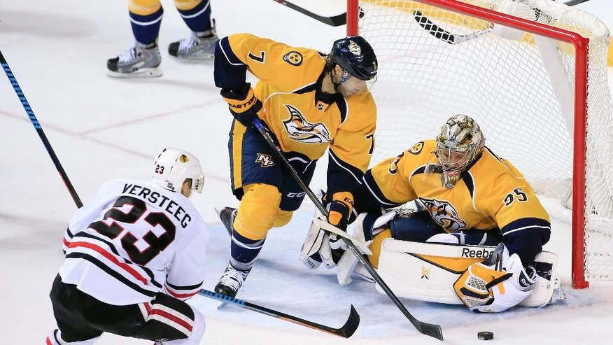 Nashville Predators center Matt Cullen (7) clears the puck away in front of goalie Pekka Rinne (35), of Finland, as Chicago Blackhawks right wing Kris Versteeg (23) closes in in the second period of an NHL hockey game Saturday, Dec. 6, 2014, in Nashville, Tenn. (AP Photo/Mark Humphrey)