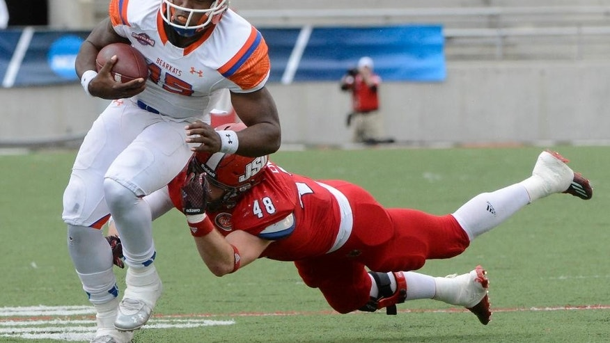 Sam Houston State quarterback Jared Johnson escapes the tackle of Jacksonville State linebacker Ben Endress in the second quarter of an NCAA FCS college football second-round playoff game in Jacksonville, Ala., Saturday, Dec. 6, 2014. (AP Photo/AL.com, Mark Almond) MAGAZINES OUT