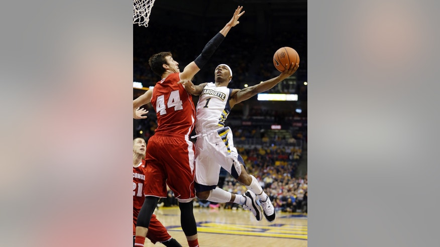 Marquette Golden's Duane Wilson, right, shoots against Wisconsin's Frank Kaminsky during the first half of an NCAA college basketball game Saturday, Dec. 6, 2014, in Milwaukee. (AP Photo/Morry Gash)