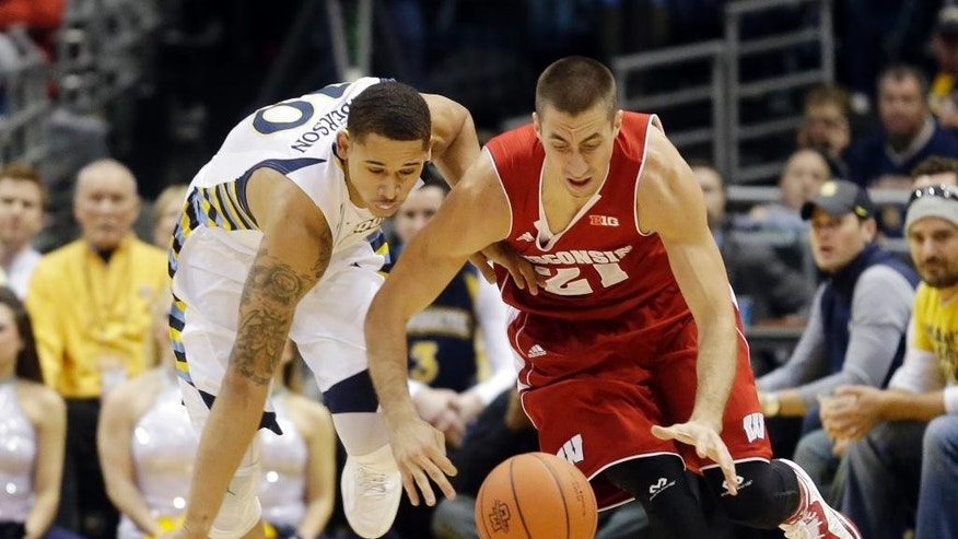 Marquette's Juan Anderson and Wisconsin's Josh Gasser (21) go after a loose ball during the first half of an NCAA college basketball game Saturday, Dec. 6, 2014, in Milwaukee. (AP Photo/Morry Gash)