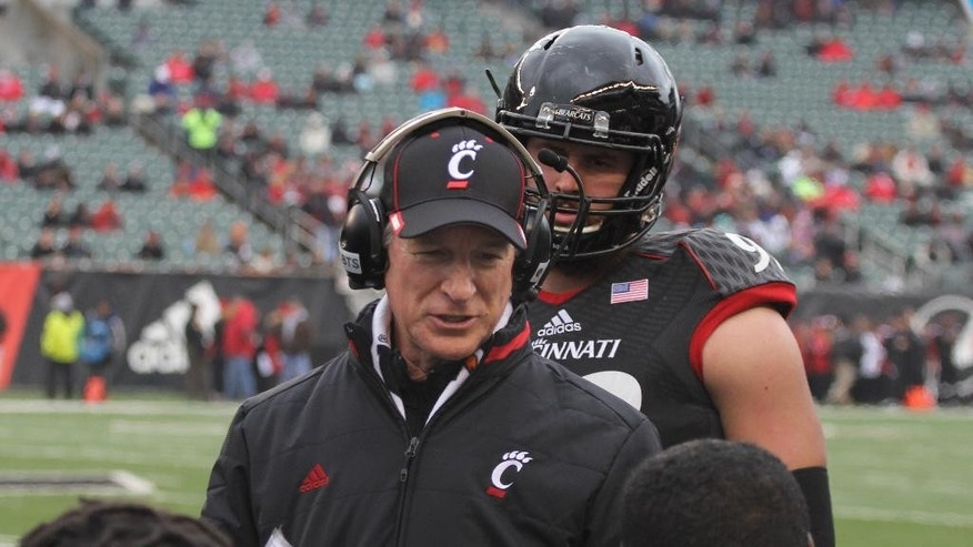 Cincinnati coach Tommy Tubberville talks with players during the first half of their NCAA college football game against Houston, Saturday Dec. 6, 2014, in Cincinnati. (AP Photo/Tom Uhlman)