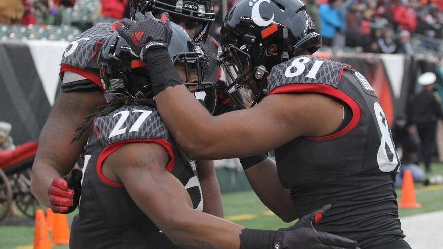 Cincinnati's Mike Boone, left, gets congratulated by DJ Dowdy after scoring a touchdown in the first half of an NCAA college football game against Houston, Saturday Dec. 6, 2014, in Cincinnati. (AP Photo/Tom Uhlman)