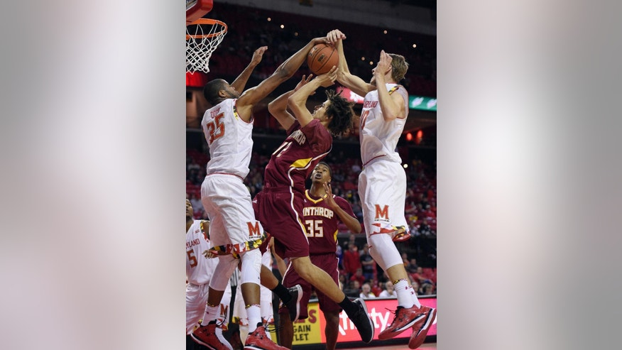 Maryland forward Damonte Dodd, left, and Jake Layman, right, block Winthrop guard Xavier Cooks (12) way to the basket during the first half of an NCAA college basketball game, Saturday, Dec. 6, 2014, in College Park, Md. (AP Photo/Nick Wass)