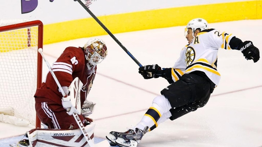 Boston Bruins' Chris Kelly, right, skates into the puck before colliding with Arizona Coyotes' Devan Dubnyk, left, during the first period of an NHL hockey game Saturday, Dec. 6, 2014, in Glendale, Ariz. (AP Photo/Ross D. Franklin)