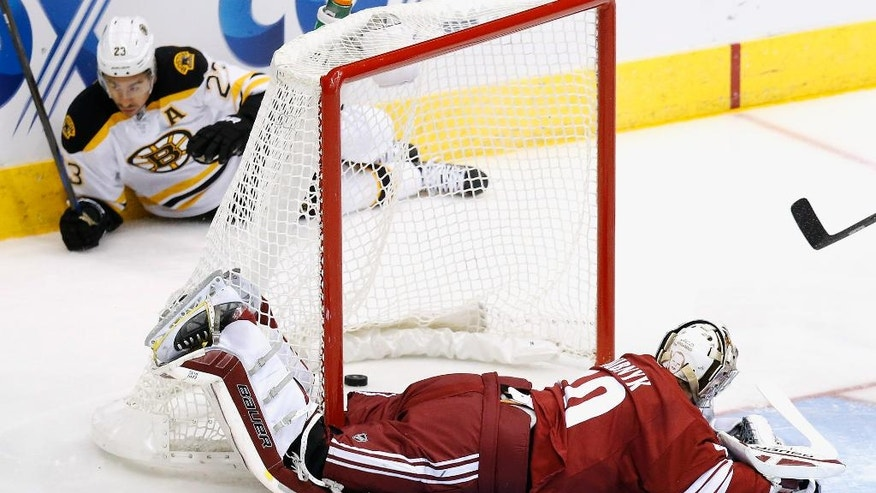 The puck finds its way behind Arizona Coyotes' Devan Dubnyk, right, and into the goal on a shot by Boston Bruins' Chris Kelly (23), during the first period of an NHL hockey game Saturday, Dec. 6, 2014, in Glendale, Ariz. The goal was waved off as it was determined the goal came off it's anchor to the ice. (AP Photo/Ross D. Franklin)