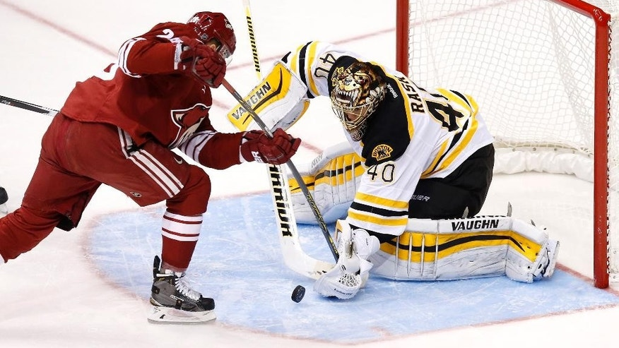 Boston Bruins' Tuukka Rask (40), of Finland, knocks the puck away with his glove on a shot by Arizona Coyotes' Lauri Korpikoski, left, of Finland, during the first period of an NHL hockey game Saturday, Dec. 6, 2014, in Glendale, Ariz. (AP Photo/Ross D. Franklin)