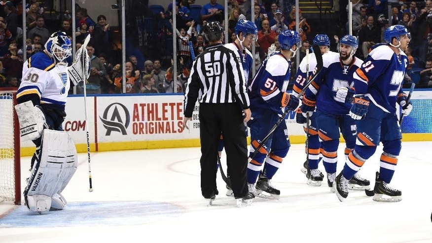 New York Islanders center Frans Nielsen (51) and defenseman Nick Leddy (2) celebrate John Tavares's (91) goal as St. Louis Blues goalie Martin Brodeur (30) reacts in the second period of an NHL hockey game Saturday, Dec. 6, 2014, in Uniondale, N.Y. (AP Photo/Kathy Kmonicek)