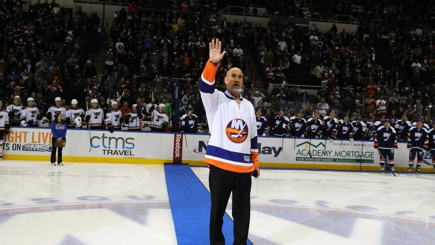 Former New York Islanders' Bobby Nystrom waves to fans before he drops a ceremonial puck before the start of an NHL hockey game at Nassau Coliseum on Saturday, Dec. 6, 2014, in Uniondale, N.Y. Nystrom was honored before the game. (AP Photo/Kathy Kmonicek)