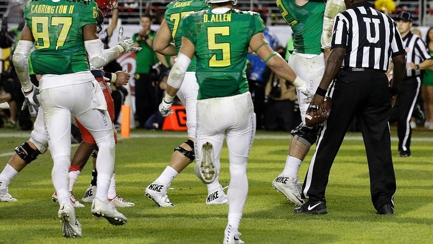 Oregon quarterback Marcus Mariota (8) is lifted by Matt Pierson (62) after Mariota scored a touchdown against Arizona in the second half of a Pac-12 Conference championship NCAA college football game Friday, Dec. 5, 2014, in Santa Clara, Calif. Oregon won the game, 51-13. (AP Photo/Ben Margot)