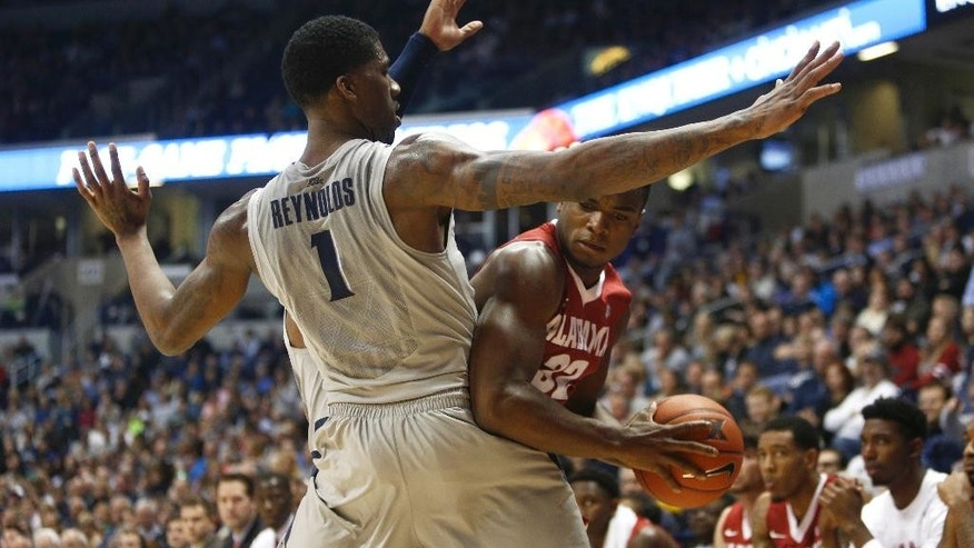 Alabama guard Retin Obasohan (32) is pressured by Xavier forward Jalen Reynolds (1) in the first half of an NCAA college basketball game, Saturday, Dec. 6, 2014, in Cincinnati. (AP Photo/David Kohl)