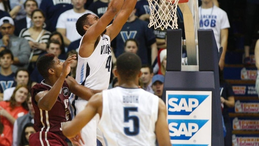 Villanova guard Darrun Hilliard II (4) dunks the ball from a pass by guard Phil Booth (5) as Saint Joseph's guard Aaron Brown (2) tries to defend during the first half of an NCAA basketball game, Saturday, Dec. 6, 2014, in Villanova. (AP Photo/Chris Szagola)
