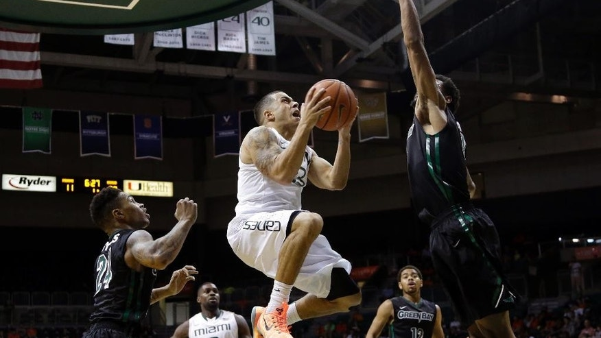 Miami guard Angel Rodriguez, center, shoots as Green Bay guard Keifer Sykes (24) and forward Greg Mays, right, defend in the first half of an NCAA college basketball game, Saturday, Dec. 6, 2014, in Coral Gables, Fla. (AP Photo/Lynne Sladky)