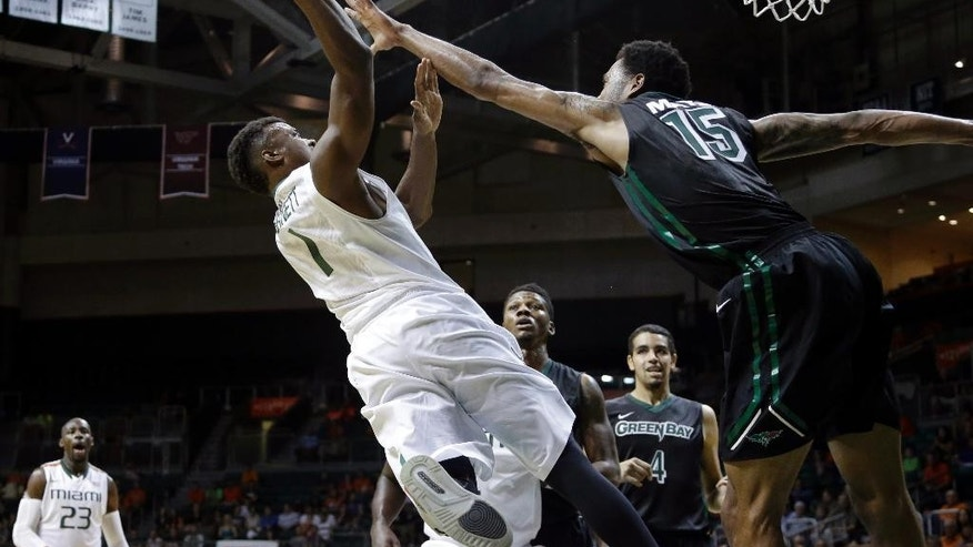 Miami guard Deandre Burnett (1) shoots as Green Bay forward Greg Mays (15) defends in the first half of an NCAA college basketball game, Saturday, Dec. 6, 2014, in Coral Gables, Fla. (AP Photo/Lynne Sladky)