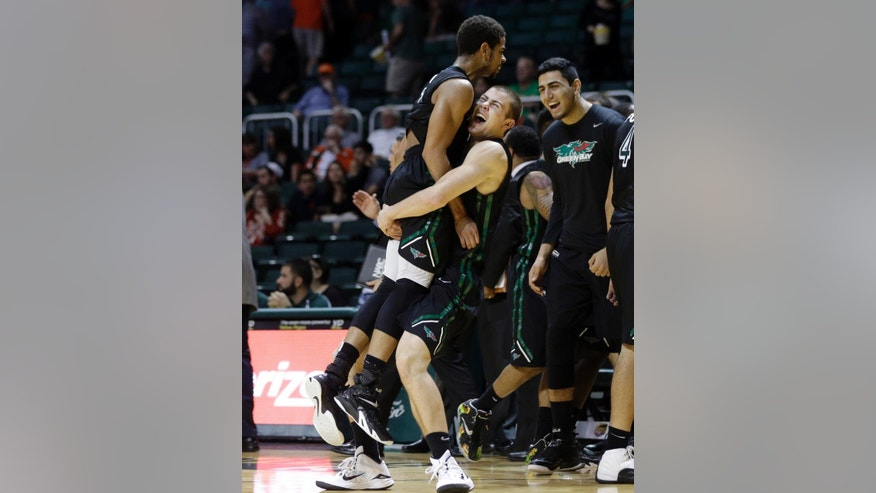 Green Bay Phoenix guard Carrington Love, left, is lifted into the air by Turner Botz, center, after Green Bay defeated Miami 68-55 in an NCAA college basketball game, Saturday, Dec. 6, 2014, in Coral Gables, Fla. (AP Photo/Lynne Sladky)