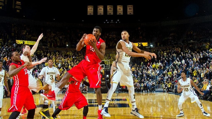 N.J.I.T. forward Daquan Holiday, center left, grabs a rebound away from Michigan guard Zak Irvin, center right, in the final second of an NCAA college basketball game in Ann Arbor, Mich., Saturday, Dec. 6, 2014. (AP Photo/Tony Ding)