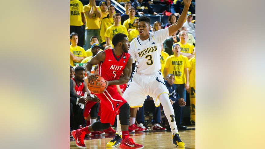 N.J.I.T. guard Damon Lynn (5) handles the ball as Michigan guard Kameron Chatman (3) defends during the second half of an NCAA college basketball game at Crisler Center in Ann Arbor, Mich., Saturday, Dec. 6, 2014. N.J.I.T. won 72-70. (AP Photo/Tony Ding)