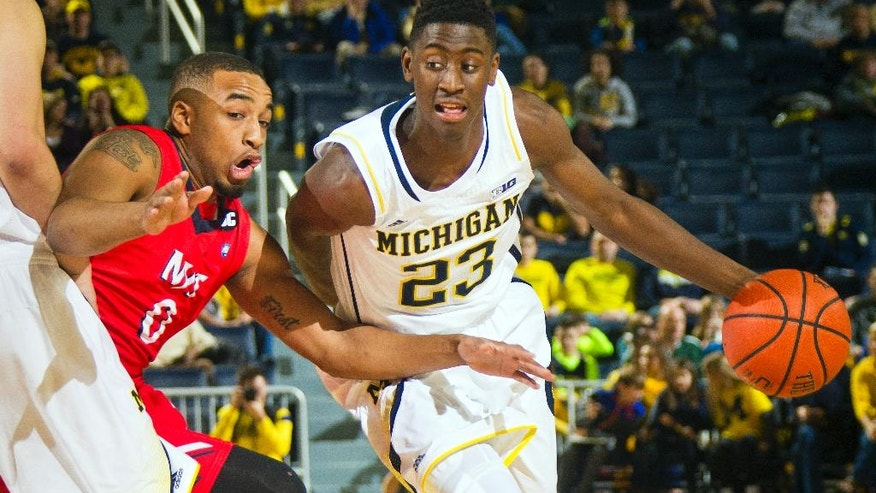 N.J.I.T. guard Ky Howard (0) defends as Michigan guard Caris LeVert (23) dribbles the ball during the first half of an NCAA college basketball game at Crisler Center in Ann Arbor, Mich., Saturday, Dec. 6, 2014. (AP Photo/Tony Ding)
