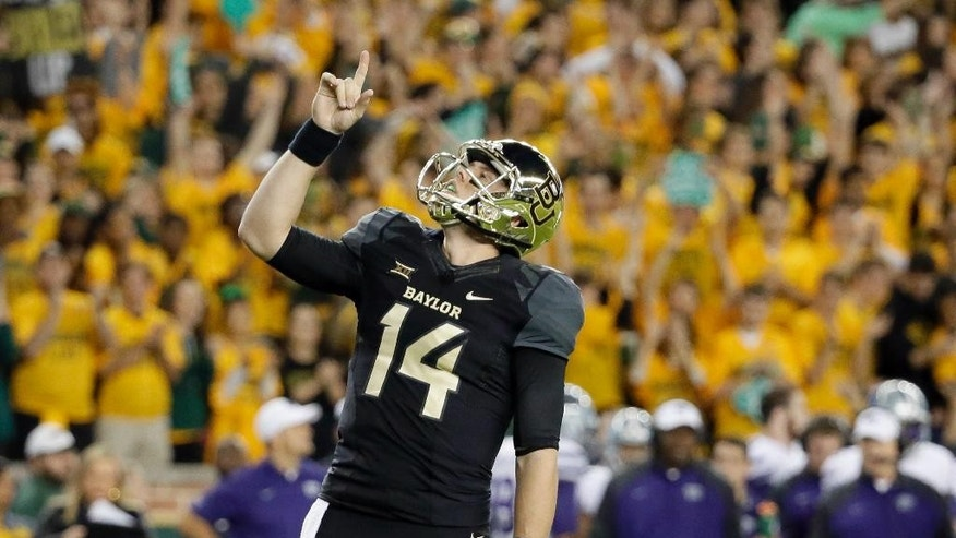 Baylor quarterback Bryce Petty (14) points skyward after a running score by running back Shock Linwood in the first half of an NCAA college football game against Kansas State, Saturday, Dec. 6, 2014, in Waco, Texas. (AP Photo/Tony Gutierrez)