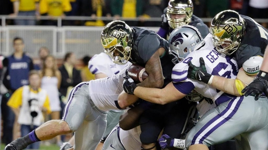 Baylor running back Shock Linwood (32) drags Kansas State defenders into the end zone for a score during the first half of an NCAA college football game, Saturday, Dec. 6, 2014, in Waco, Texas. (AP Photo/Tony Gutierrez)