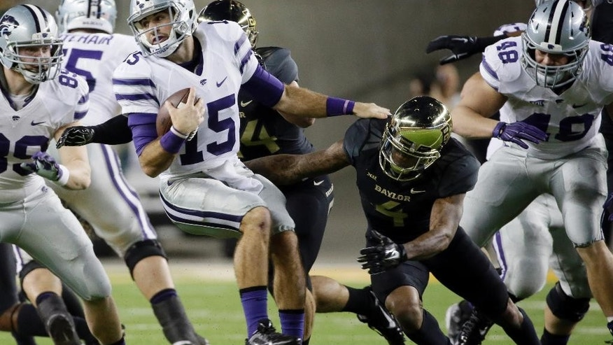 Kansas State quarterback Jake Waters (15)  is chased down and sacked by Baylor's Bryce Hager, center rear, and Xavien Howard (4) in the first half of an NCAA college football game, Saturday, Dec. 6, 2014, in Waco, Texas. (AP Photo/Tony Gutierrez)