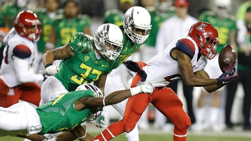 Arizona's Tyrell Johnson, right, fumbles the ball as he is tackled by Oregon's Ifo Ekpre-Olomu during the first half of a Pac-12 Conference championship NCAA college football game Friday, Dec. 5, 2014, in Santa Clara, Calif. (AP Photo/Ben Margot)