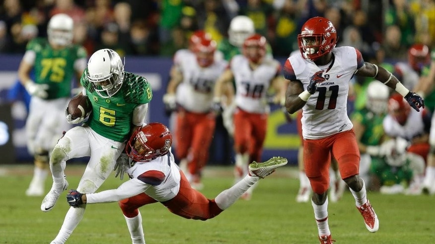 Oregon's Charles Nelson (6) breaks the tackle of  Arizona's Jamar Allah during the first half of a Pac-12 Conference championship NCAA college football game Friday, Dec. 5, 2014, in Santa Clara, Calif. At right is Arizona's William Parks (11). (AP Photo/Ben Margot)