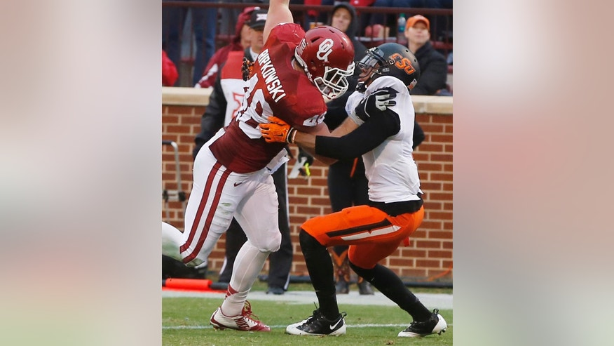 Oklahoma fullback Aaron Ripkowski (48) moves past Oklahoma State cornerback Kevin Peterson, right, and scores a touchdown in the second quarter of an NCAA college football game in Norman, Okla., Saturday, Dec. 6, 2014. (AP Photo/Sue Ogrocki)