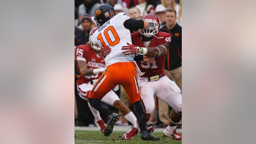 Oklahoma State quarterback Mason Rudolph (10) is tackled by Oklahoma defensive end Charles Tapper (91) in the second quarter of an NCAA college football game in Norman, Okla., Saturday, Dec. 6, 2014. (AP Photo/Sue Ogrocki)