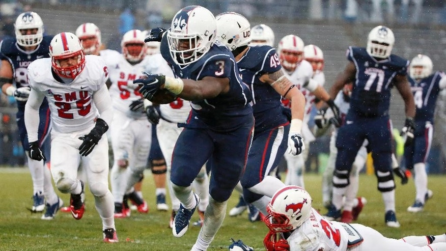 Connecticut running back Ron Johnson (3) breaks a tackle from SMU defensive back Darrion Richardson, lower right, and runs in for a touchdown during the second quarter of an NCAA college football game in East Hartford, Conn., Saturday, Dec. 6, 2014. (AP Photo/Michael Dwyer)