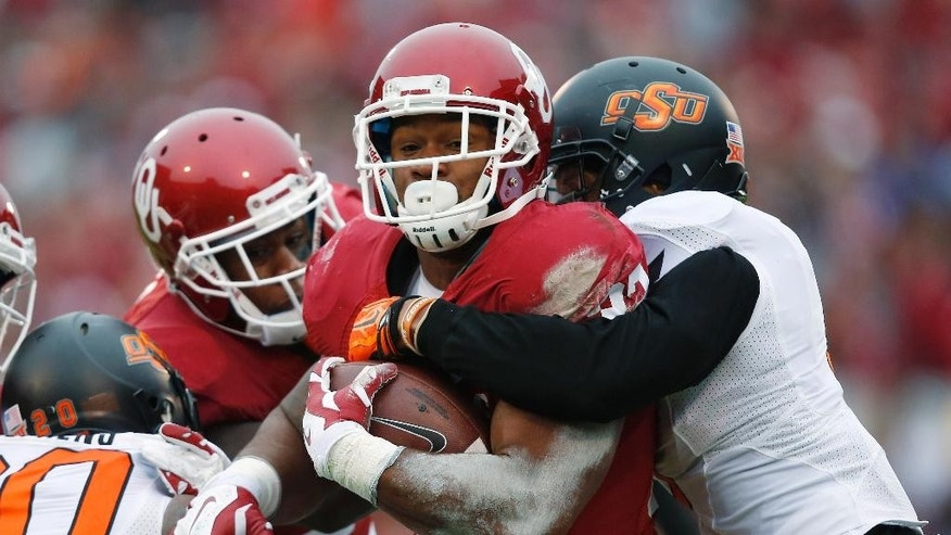 Oklahoma running back Samaje Perine, center, is tackled by Oklahoma State safety Larry Stephens, left, and cornerback Kevin Peterson, right, in the first quarter of an NCAA college football game in Norman, Okla., Saturday, Dec. 6, 2014. (AP Photo/Sue Ogrocki)