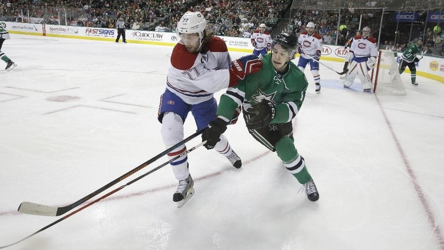 Montreal Canadiens defenseman Tom Gilbert (77) and Dallas Stars left wing Curtis McKenzie (11) skate for the loose puck during the first period of an NHL hockey game Saturday, Dec. 6, 2014, in Dallas. (AP Photo/LM Otero)