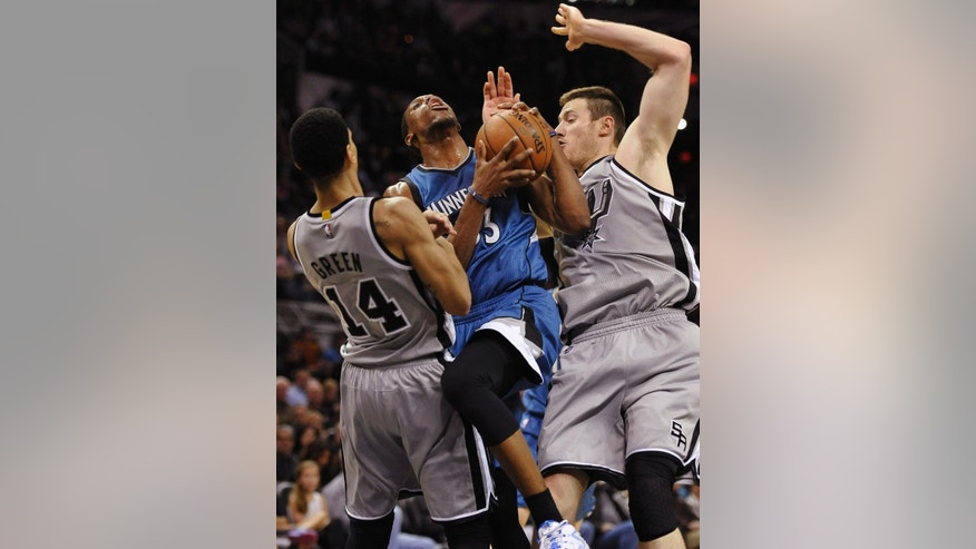 Minnesota Timberwolves forward Thaddeus Young, center, collides with San Antonio Spurs forwards Danny Green, left, and Aron Baynes, of Australia, during the first half of an NBA basketball game, Saturday, Dec. 6, 2014, in San Antonio. (AP Photo/Darren Abate)