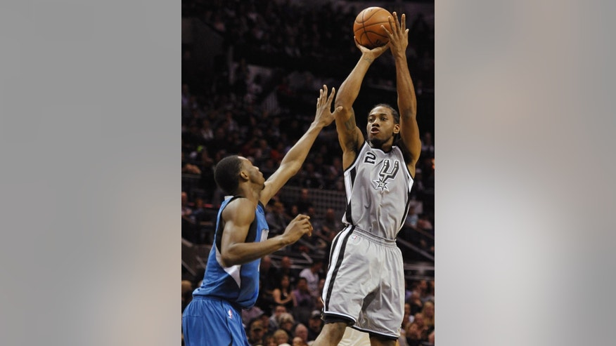 San Antonio Spurs forward Kawhi Leonard, right, shoots against Minnesota Timberwolves guard Andrew Wiggins during the first half of an NBA basketball game, Saturday, Dec. 6, 2014, in San Antonio. (AP Photo/Darren Abate)