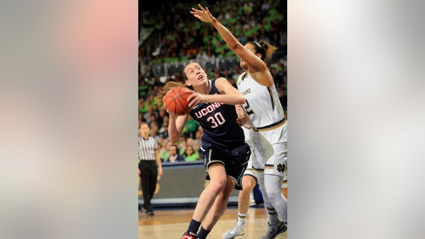 Connecticut forward Brenna Stewart, left, drives the lane while Notre Dame forward Taya Reimer defends in the first half of  an NCAA college basketball game, Saturday Dec. 6, 2014, in South Bend, Ind. (AP Photo/Joe Raymond)
