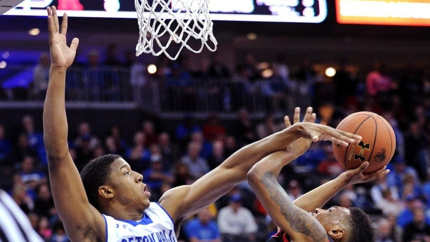Seton Hall forward Desi Rodriguez, left, attempts to block a shot by Rutgers guard Miles Mack during the first half of an NCAA college basketball game, Saturday, Dec. 6, 2014, in Newark, N.J. (AP Photo/Bill Kostroun)